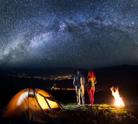 Night camping. Young pair hikers holding hands, standing near bonfire and enjoying starry sky. In the background luminous village in the valley. Low light