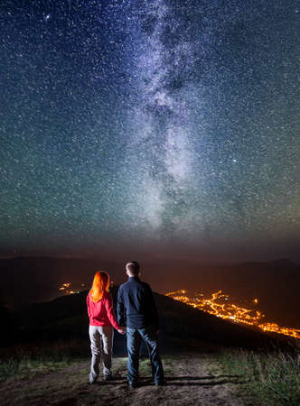 starry night: Tourist family - man and woman holding hands, standing on a hill and enjoying amazing starry sky, Milky way and luminous village in the valley. Long exposure Stock Photo