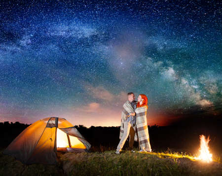 Happy couple backpackers together covered with a plaid standing near campfire and tent at night and enjoying starry sky. Milky way