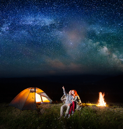 Guy showing red-haired girl at the stars and Milky way in the sky. Couple sitting near the glowing tent. Long exposure. Astrophotography