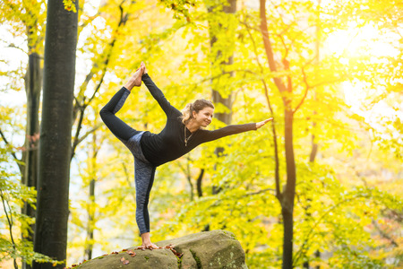 Sporty happy woman is practicing yoga and doing asana Narajasana in the autumn forest on the big boulder
