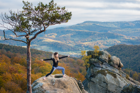 Sporty attractive female is practicing yoga and doing asana Virabhadrasana 2 on the top of the mountain near big tree. Autumn forests, rocks and hills on the background