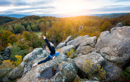 pada: Attractive slim girl is practicing yoga and doing asana Eka Pada Rajakapotanasana on the top of the high rock in the evening. Autumn forests, rocks and hills on the background
