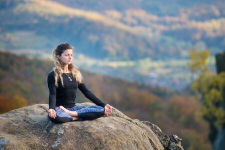 Happy slim girl is practicing yoga and doing asana Siddhasana on the top of the mountain. Autumn forests, rocks and hills on the background Standard-Bild