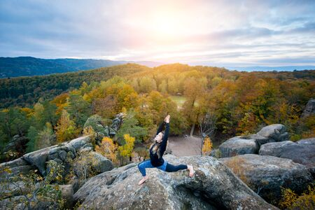 Flexible fit woman is practicing yoga and doing asana Virabhadrasana 1 on the top of the huge boulder in the evening. Autumn forests, rocks and hills on the background