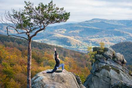 Sporty young woman is practicing yoga and doing asana Virabhadrasana 1 on the top of the mountain near big tree. Autumn forests, rocks and hills on the background