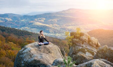 Sporty young female is practicing yoga and doing asana Siddhasana on the top of the mountain in the evening. Autumn forests, rocks and hills on the background