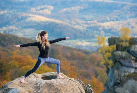 Happy young woman is practicing yoga and doing asana Virabhadrasana II on the top of the mountain. Autumn forests, rocks and hills on the background