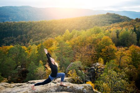 Happy fit woman is practicing yoga and doing asana Virabhadrasana 1 on the top of the high rocky mountain in the evening. Autumn forests, rocks and hills on the background