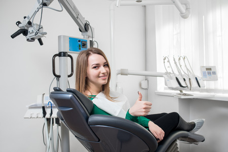 odontology: Happy female patient with braces on teeth sitting in dental chair, smiling and showing thumbs up after treatment at modern dental clinic. Dentistry, medicine and healthcare concept. Stock Photo