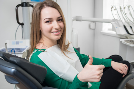 Young female patient with braces on teeth sitting in dental chair, smiling and showing thumbs up after treatment at modern dental clinic. Dentistry, medicine and healthcare concept.
