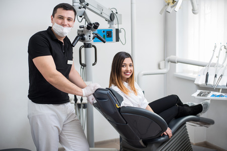 whiten: Handsome male dentist with beautiful female patient after treatment in modern dental clinic. Woman sitting in the dental chair. Dentistry. Stomatology equipment