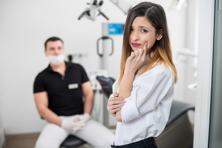 treating: Young woman suffering from terrible teeth pain, touching cheek with hand at dental clinic. Female feeling toothache. On the background dentist sitting on the chair. Dental care and health concept