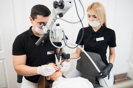 Male dentist and female assistant treating patient teeth with dental tools - microscope, mirror and probe at dental clinic office. Medicine, dentistry and health care concept. Dental equipment