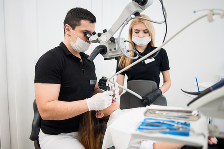 whiten: Male dentist and female assistant treating patient teeth with dental tools - microscope, mirror and drill at dental clinic office. Medicine, dentistry and health care concept. Dental equipment