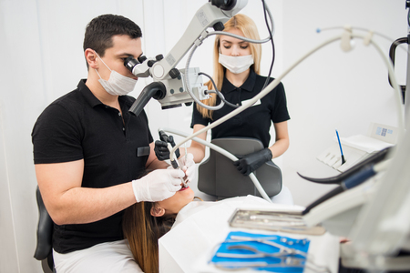 treating: Male dentist and female assistant treating patient teeth with dental tools - microscope, mirror and drill at dental clinic office. Medicine, dentistry and health care concept. Dental equipment