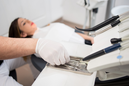 scaler: Dentist with gloved hands is treating patient with dental tools in dental office. Dentistry. Selective focus on the tools