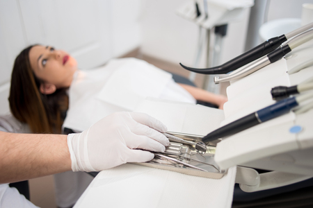 Dentist with gloved hands is treating patient with dental tools in dental hospital. Dentistry. Selective focus on the tools