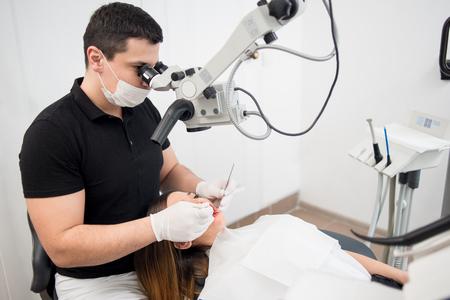 치과 도구 - 현미경, 미러 및 프로브 치과 진료소 사무실에서 환자의 이빨을 치료하는 남성 치과 의사. 의학, 치과 및 건강 관리 개념입니다. 치과 용 장