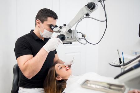 Dentista maschio con strumenti dentali - microscopio, specchio e sonda che controlla i denti pazienti presso l'ufficio clinico dentale. Concetto di medicina, odontoiatria e assistenza sanitaria. Attrezzature dentali