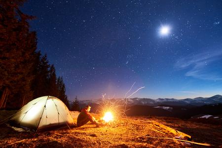 Mannelijke toerist rust in zijn kamp 's nachts, zittend in de buurt van kampvuur en tent onder prachtige nachtelijke hemel vol met sterren en de maan en genieten van de nachtscène in de bergen Stockfoto