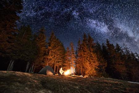 男性の観光客は、夜の森の近くの彼の陣営の残りを持っています。キャンプファイヤーと美しい夜満天の星や、天の川の下でテントのそばに座って 写真素材