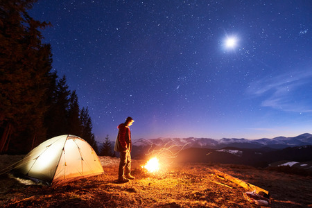 Male tourist have a rest in his camp at night, standing near campfire and tent under beautiful night sky full of stars and the moon and enjoying night scene in the mountains. Long exposure Stok Fotoğraf