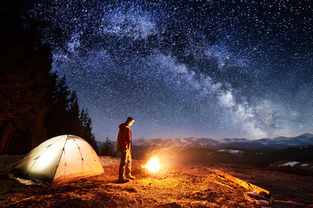 Male hiker have a rest in his camp near the forest at night. Man standing near campfire and tent under beautiful night sky full of stars and milky way. Long exposure Foto de archivo
