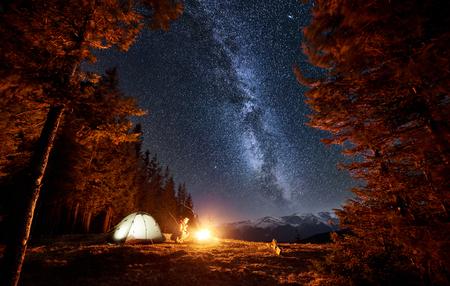 Turista masculino tiene un descanso en su campamento cerca del bosque por la noche. Hombre sentado cerca de fogata y carpa bajo el hermoso cielo nocturno lleno de estrellas y la vía láctea. Larga exposición