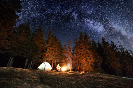 Male tourist enjoying in his camp near the forest at night. Man sitting near campfire and tent under beautiful night sky full of stars and milky way. Astrophotography Stock Photo