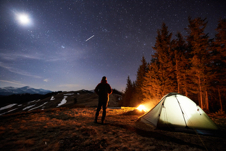 Male tourist have a rest in his camp near the forest at night. Man standing near campfire and tent under beautiful night sky full of stars and the moon, and enjoying night scene