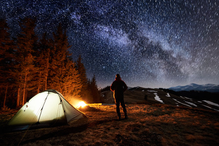 Male tourist have a rest in his camp near the forest at night. Man standing near campfire and tent under beautiful night sky full of stars and milky way, and enjoying night scene. Long exposure