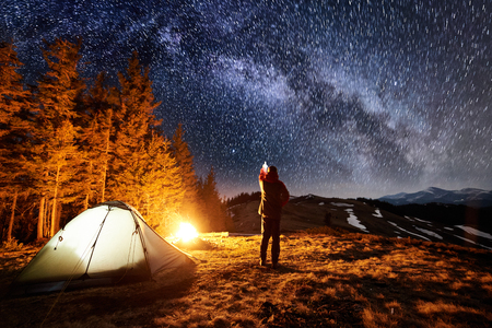 Male tourist have a rest in his camp near the forest at night. Man standing near campfire and tent, pointing at beautiful night sky full of stars and milky way