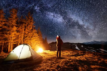 Turista masculino tiene un descanso en su campamento cerca del bosque por la noche. Hombre de pie junto a la fogata y la tienda, apuntando al hermoso cielo nocturno lleno de estrellas y la vía láctea Foto de archivo