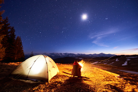 Male tourist have a rest in his camp at night near campfire and tent under beautiful night sky full of stars and the moon and enjoying night scene in the mountains Stock Photo