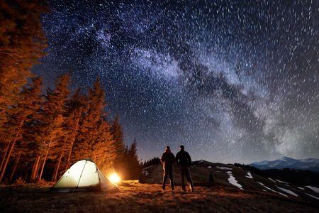 Two male tourists have a rest in the camping near the forest at night. Guys standing near campfire and tent under beautiful night sky full of stars and milky way, enjoying night scene. Long exposure Archivio Fotografico
