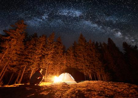 El turista masculino tiene un resto en su campo cerca del bosque por la noche. Individuo que se sienta cerca de la hoguera y de la carpa bajo el cielo nocturno hermoso por completo de las estrellas y de la manera lechosa. Larga exposición