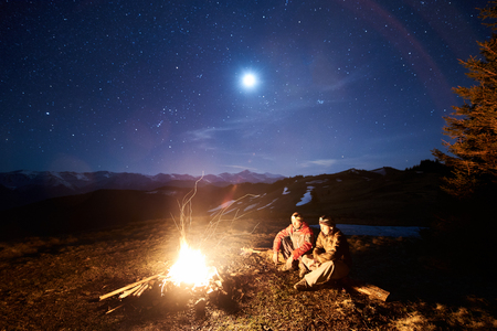 Two male tourists have a rest in his camp near the forest at night. Guys sitting near campfire and tent under beautiful night sky full of stars and the moon, and enjoying night scene in the mountains Stock Photo