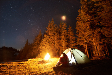 Male tourist have a rest in his camp near the forest at night. Man sitting near campfire and tent under beautiful night sky full of stars and enjoying night scene
