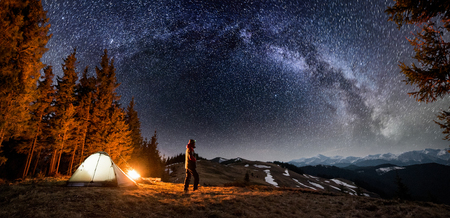 Male tourist have a rest in his camp near the forest at night. Man standing near campfire and tent under beautiful night sky full of stars and milky way, and enjoying night scene. Panoramic landscape