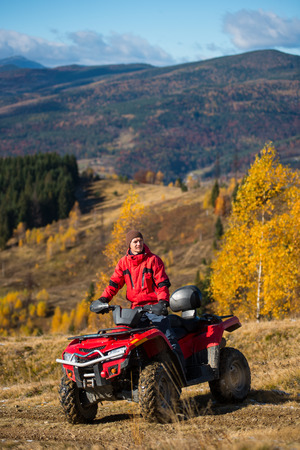 Man on quad bike in the mountains on a blurred background mighty mountains and forests in the autumn sunny day