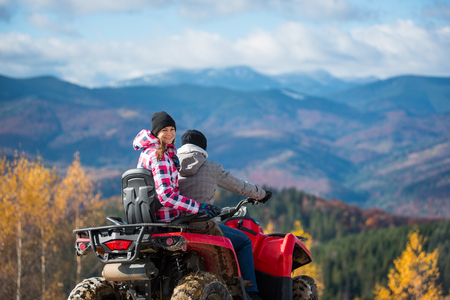 Guy driving ATV, girl sitting behind him and turned around, looking at the camera and smiling. Beautiful landscape mountains at autumn sunny day on blurred background