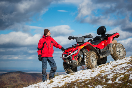 cirrus: Beautiful landscape of blue sky with cirrus clouds in front of a man standing in winter clothes near atv on a snowy hill