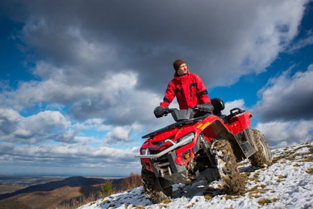 Bottom view of a guy on the sports atv quad bike at the snow-covered slope against the blue cloudy sky on a sunny day in the mountains