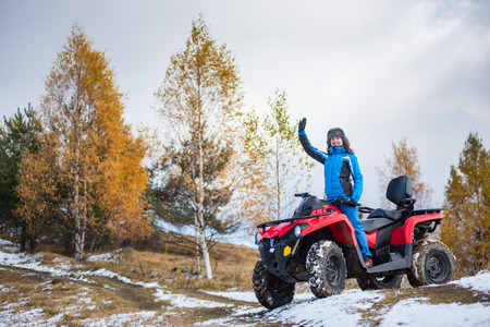 Happy girl in blue winter clothes waving on a red quadbike atv on snow-covered hill against autumn nature on the background with copy space