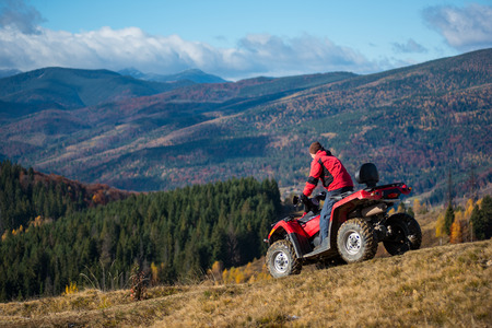 Man riding down on an ATV the hilly road on a background of mountains, forest and blue sky. The concept of an active holiday in the mountains Standard-Bild