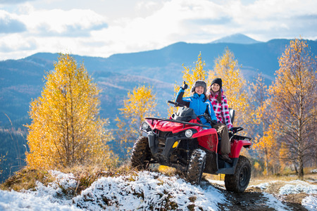 Two women riders ATV in jackets and hats on a snow-covered trail at sunny autumn day against trees with yellow leaves and mountains. First woman showing thumbs up. Blurred background Stock Photo