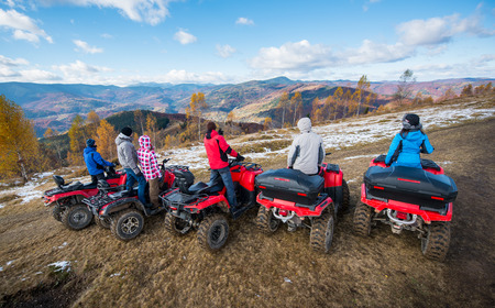 Rear view of a group of people on red quad bikes at hill enjoying open views of the mountains under the blue sky in autumn