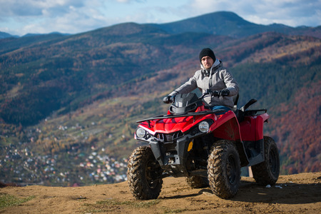 Guy in winter clothes on a red quad bike on a mountain top looking at the camera. Blurred background of mountain scenery Stock Photo