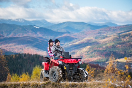 Happy couple in winter sporty clothing on red four-wheeler ATV in mountains, girl sitting behind man and hugging him. Beautiful landscape of mountains and forest at sunny autumn day